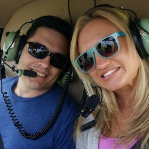 Man and Woman smiling in helicopter