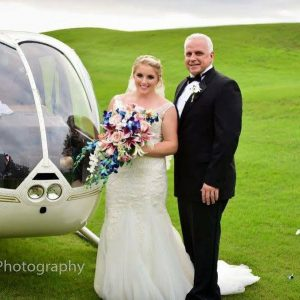 bride and father of the bride next to helicopter
