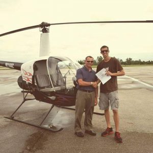 Helicopter pilot handing certificate to trainee