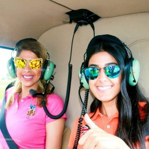 two women wearing sunglasses and smiling in helicopter