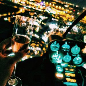 woman's hand holding champagne in helicopter