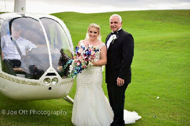 bride and father of the bride standing next to helicopter