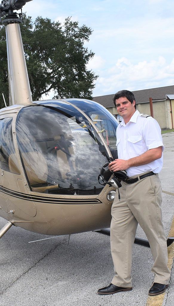 Cole Maguire standing next to a helicopter